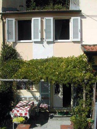 Fassade mit Terrasse neben der Küche und antike Sonnenuhr auf der Fassade