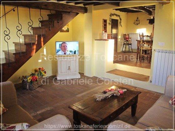 Wohn-/TV-Zimmer mit Durchgang ins Kaminzimmer und Holzstiege in die erste Etage. Tisch aus der 2. Hälfte des 18. Jh.