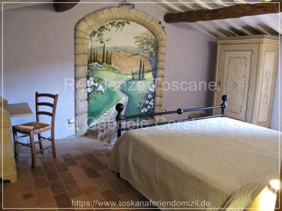 Highlight des Hauses: Doppelzimmer mit einem Tromp-l`oeil-Wandbild, das eine fiktive toskanische Landschaft darstellt.