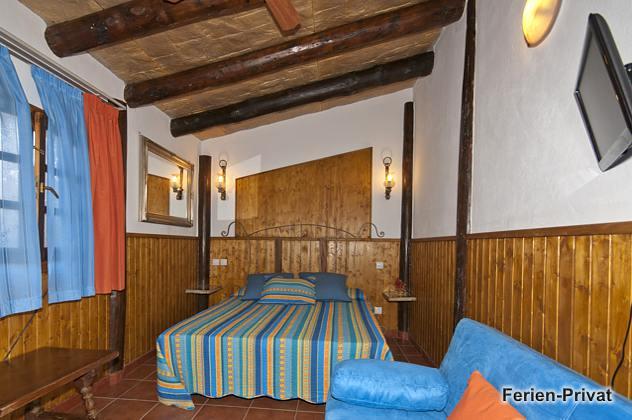 Schlafzimmer mit Doppelbett und Sofa