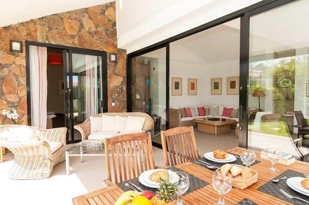überdachte Terrasse mit gemütlicher Sitzecke und Esstisch
