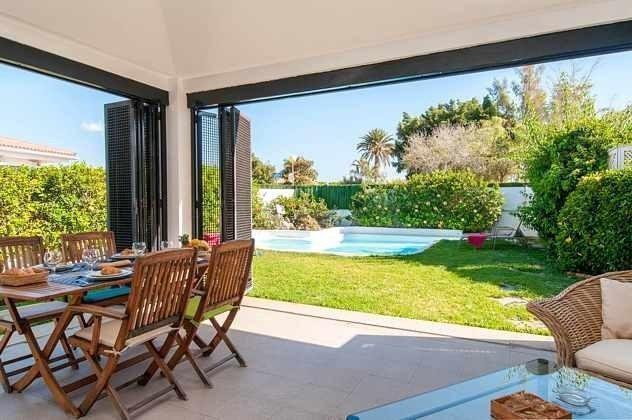 überdachte Terrasse mit Blick zum Garten und Pool