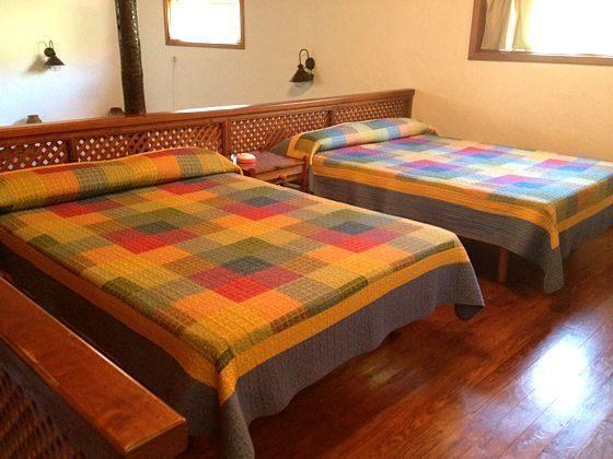 Schlafzimmer mit zwei Einzelbetten über dem Wohnbereich