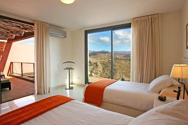 Schlafzimmer mit zwei Einzelbetten im Obergeschoss mit Zugang zur oberen Terrasse