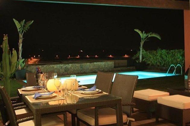 Blick abends von der Terrasse zum beleuchteten Pool