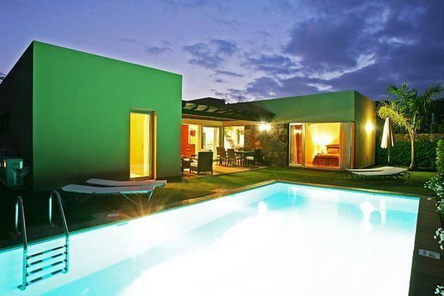 beleuchteter Pool und Haus am Abend