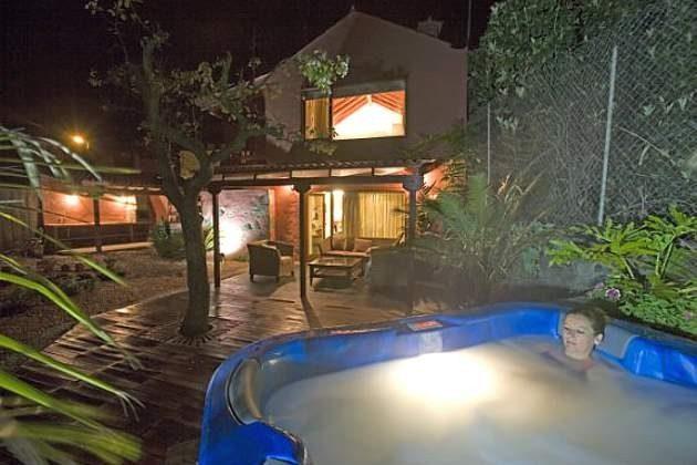 Haus, Terrasse, Grillplatz und Whirlpool abends beleuchtet