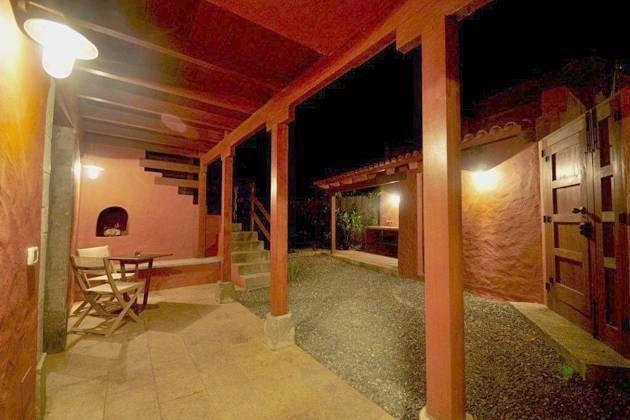 seitliche Terrasse abends, daneben Eingangspforte und Grillplatz