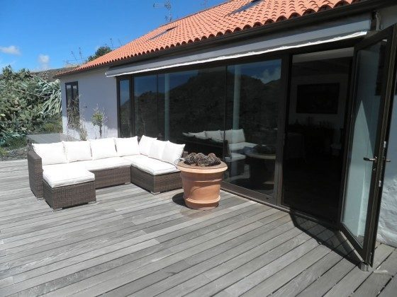 windgeschützte Terrasse mit gemütlichen Rattan-Möbeln