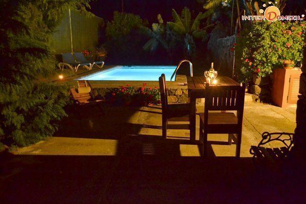 beleuchteter Pool und Terrasse abends