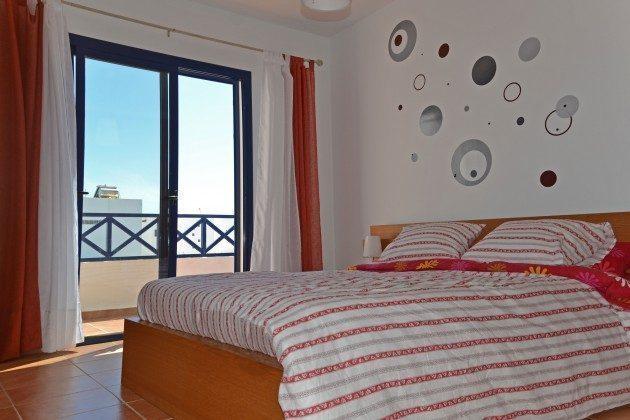 Schlafzimmer mit Doppelbett und kleinem Balkon