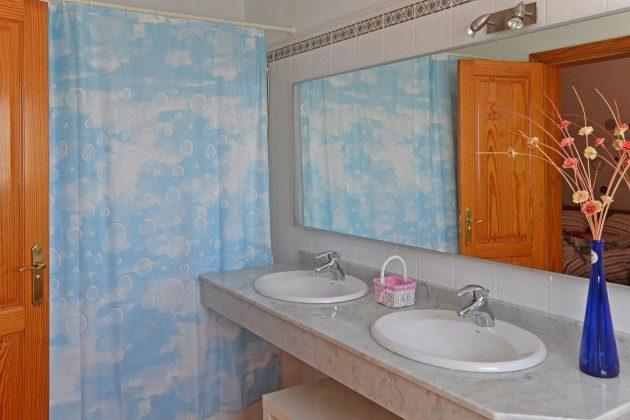 eines der Badezimmer mit Doppelwaschtisch und Wanne