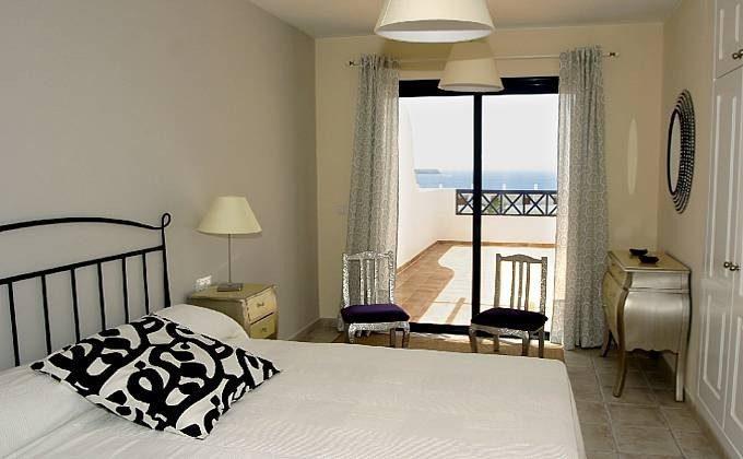Schlafzimmer mit Doppelbett und Zugang zu einer der oberen Terrassen