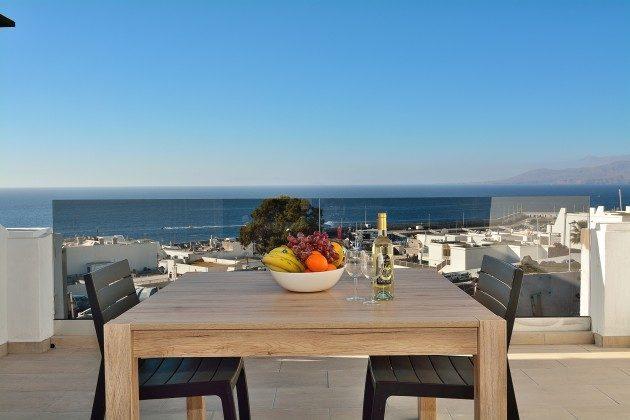 LZ 110068-85 Wohnbeispiel Terrasse mit Meerblick und Gartenmöbeln