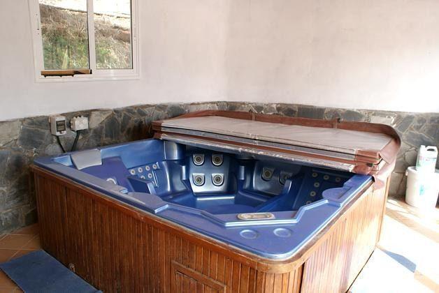 Whirlpool geschützt in einem kleinem Haus mit Blick zum Pool