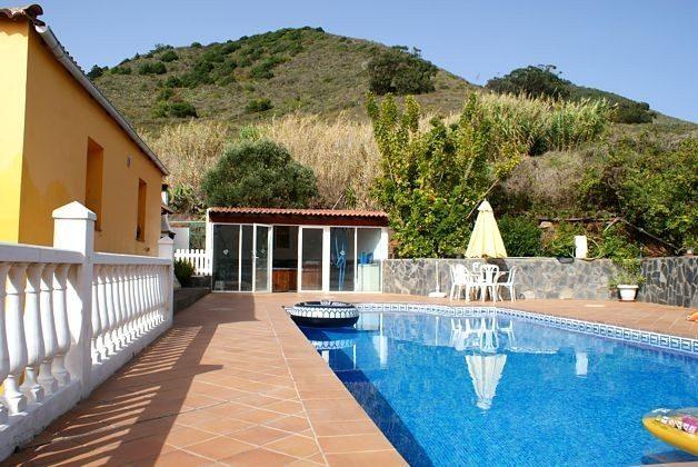 Außenbereich mit Pool und hinten im Bild Haus mit Whirlpool