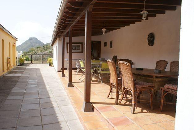 überdachte, geschützte Terrasse mit Gartenmöbeln